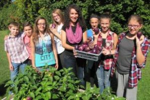 Jennifer Grant stands with some students at St. George's School in Long Sault, showing off their garden.